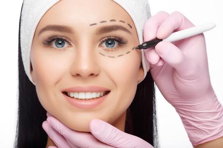 Plastische Chirurgie Frau Gesicht. Gesicht der Frau, markiert für plastische Gesichtschirurgie. Junge Frau mit Perforationslinien auf ihrem Gesicht vor der plastischen Chirurgie Betrieb. Kosmetikerin berühren Frau Gesicht.