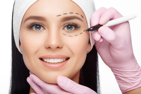 Plastic surgery woman face. Woman's face, marks for facial plastic surgery. Young woman with perforation lines on her face before plastic surgery operation. Beautician touching woman face.
