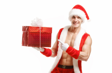 Fitness Santa shows a red box. Muscular Santa Claus holding a Christmas present in red box. Fitness Santa Happy New Year. Bodybuilder Santa with a red box on a white background. Sexy Santa Claus