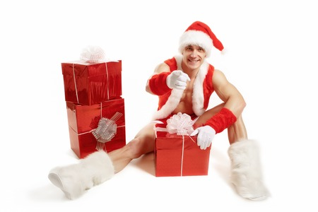 newyear: Muscular Santa Claus sitting with Christmas gifts in red. Fitness Santa Happy New Year. Bodybuilder Santa with a red box on a white background. Sexy Santa Claus pointing her finger Stock Photo