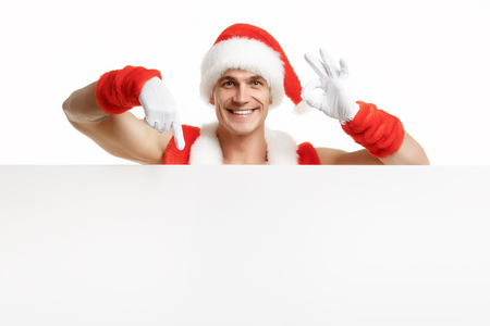 Santa Claus with a banner sales. Joyful santa claus points to the banner sales. Merry Fitness Santa isolated on white background. Christmas banner sales. Christmas sale.