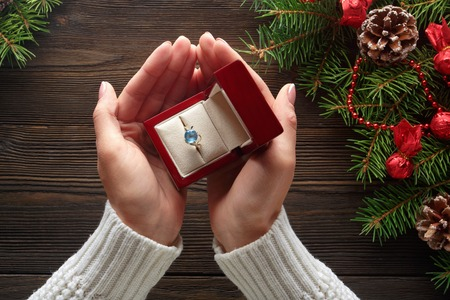 Christmas background. Engagement ring in female hands among Christmas decorations on wood background. Romance, jewelry concept - woman hands with wedding ring in gift box. Gift on Valentines Day Stock Photo