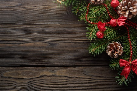 Christmas wooden background with Christmas tree and red decorations. Christmas Wreath with Rustic Wood Background. Christmas design - Merry Christmas. Christmas ornaments
