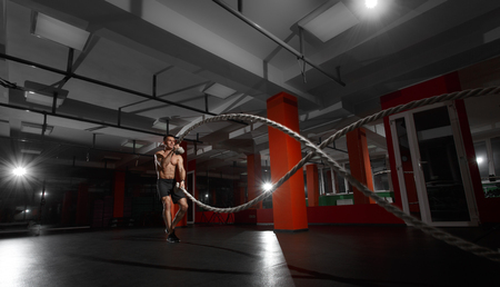 Fitness man working out with battle ropes at gym. Battle ropes fitness man at gym workout exercise fitted body. Fitness man training with battle rope in fitness club. Training with battle rope Imagens
