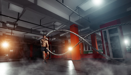 Fitness man working out with battle ropes at gym. Battle ropes fitness man at gym workout exercise fitted body. Fitness man training with battle rope in fitness club. Training with battle rope Foto de archivo