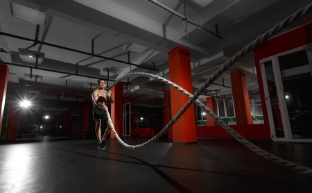 Fitness man working out with battle ropes at gym. Battle ropes fitness man at gym workout exercise fitted body. Fitness man training with battle rope in fitness club. Training with battle rope Reklamní fotografie