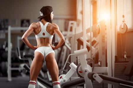 Crossfit Frau mit dem Rücken in der Turnhalle stehen. Fitness Frau, durchtrainierten Körper, Fitness-Modell. Bodybuilder Frau in der Turnhalle. Perfekte Fitness Frau sexy Gesäß in Dessous. Fitness und Bodybuilding Standard-Bild