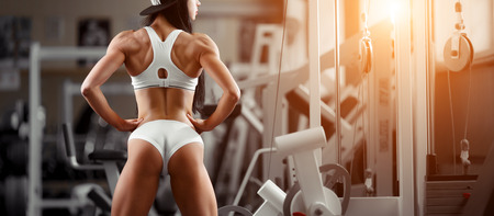 Crossfit woman standing with her back in the gym. Fitness woman, trained body, fitness model. Bodybuilder woman in the gym. Perfect fitness woman sexy buttocks in lingerie. Fitness and bodybuilding Stock Photo