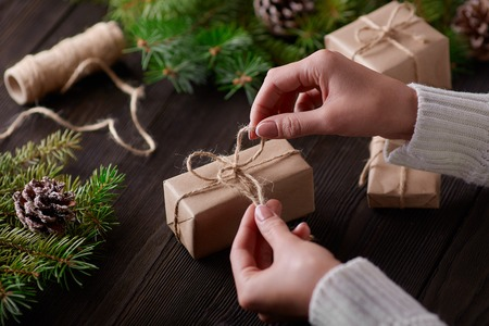 Beautiful female hands are packed Christmas gift in brown  paper, rope. Gift box in brown  paper tied with string. Christmas gift in  paper with decoration on rustic wooden background.