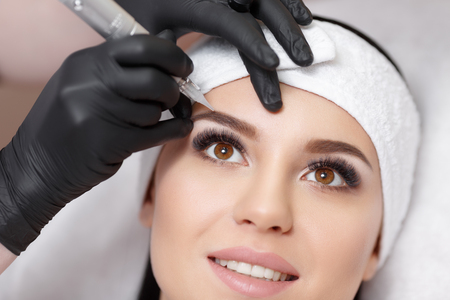 Permanent makeup. Permanent tattooing of eyebrows. Cosmetologist applying permanent make up on eyebrows- eyebrow tattoo