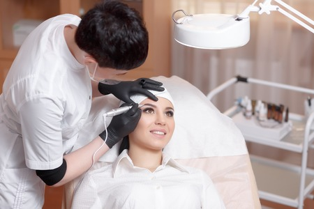 Cosmetologist applying permanent make up on eyebrows- eyebrow tattoo. Permanent make-up tattoo at beauty salon. Permanent makeup. Aesthetic medicine, cosmetology. Cosmetology and makeup salon.