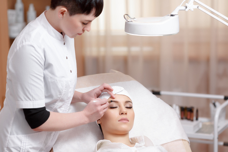 Permanente make-up. Permanente make-up wizard maakt wenkbrauw correctie procedure. Mooie jonge vrouw krijgt wenkbrauw correctie procedure. Jonge vrouw pincet haar wenkbrauwen in beauty salon Stockfoto