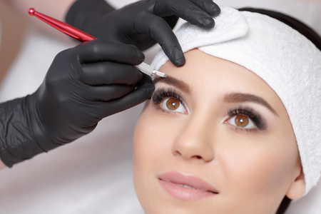 cejas maquillaje permanente. Mikrobleyding cejas flujo de trabajo en un salón de belleza. Cosmetólogo la aplicación de un maquillaje especial permanente en las cejas de una mujer. Foto de archivo