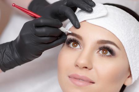 Stałe brwi makijaż. Mikrobleyding brwi przepływ pracy w salonie kosmetycznym. Kosmetolog stosując specjalny makijaż permanentny brwi na kobiecych. Zdjęcie Seryjne