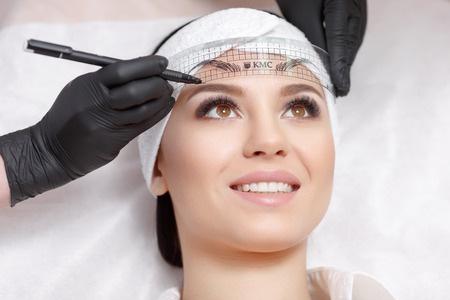 Permanent makeup eyebrows. Mikrobleyding eyebrows workflow in a beauty salon. Cosmetologist applying a special permanent makeup on a womans eyebrows. Stock Photo