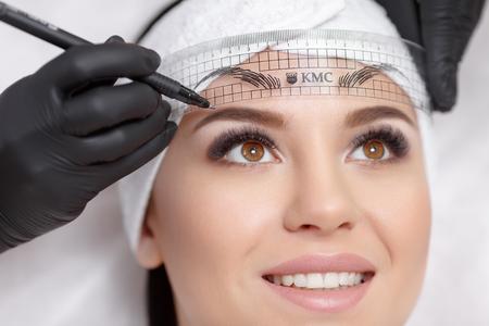 cejas maquillaje permanente. Mikrobleyding cejas flujo de trabajo en un salón de belleza. Cosmetólogo la aplicación de un maquillaje especial permanente en las cejas de una mujer.