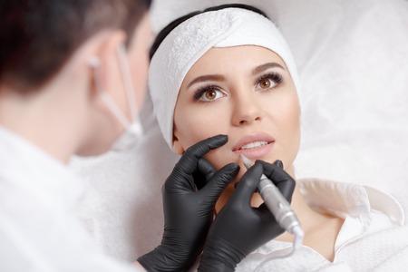 Permanent makeup lips. Permanent makeup wizard makes lips correction procedure. Beautiful young woman gets lips correction procedure. Makeup in a beauty salon Foto de archivo