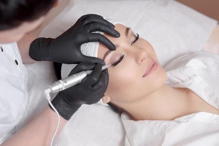 恒久的な化粧を作る美容師をクローズ アップ。彫師は、恒久的なメイクを作るします。魅力的な女性は、顔のケアとタトゥーを取得します。美容院