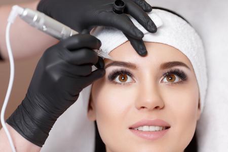Permanent Make-up. Permanent Tätowieren von Augenbrauen. Cosmetologist permanent Make-up auf Augenbrauen- Augenbraue Tattoo-Anwendung Standard-Bild - 67779570