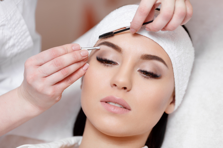 plucking: Permanent makeup. Beautiful young woman gets eyebrow correction procedure. Young woman tweezing her eyebrows in beauty saloon. Young woman plucking eyebrows with tweezers close up