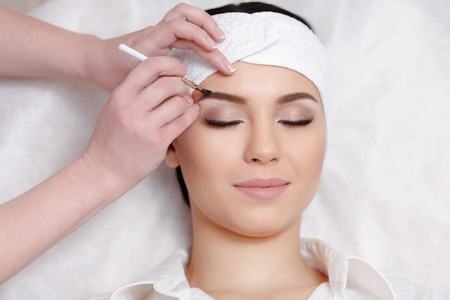 plucking: Permanent makeup. Permanent make-up wizard makes eyebrow correction procedure. Beautiful young woman gets eyebrow correction procedure. Young woman tweezing her eyebrows in beauty saloon