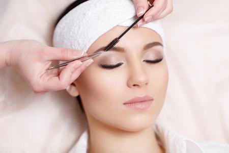 Permanente make-up. De mooie jonge vrouw krijgt de procedure van de wenkbrauwcorrectie. Jonge vrouw die haar wenkbrauwen in schoonheidssalon pincet. Jonge vrouw epileren wenkbrauwen met een pincet close-up