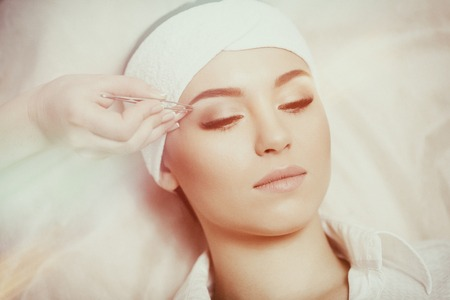 Young woman tweezing her eyebrows in beauty saloon Stock Photo