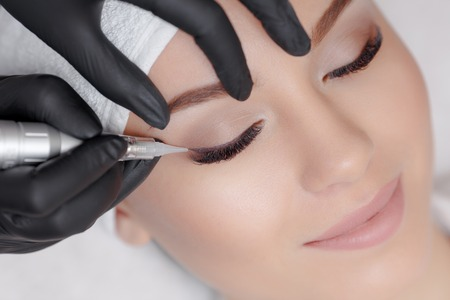 Cosmetologist making permanent makeup Stock Photo