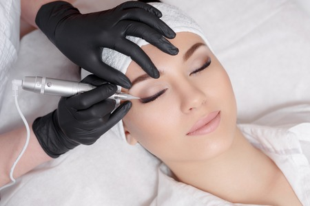Professional cosmetologist wearing black gloves making permanent makeup
