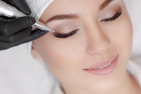 Cosmetologist het maken van permanente make up bij schoonheidssalon Stockfoto
