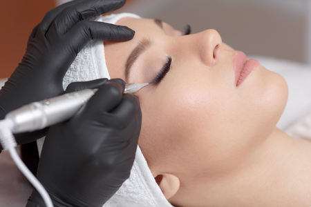 falso: Cierre de cosmetóloga haciendo delineador de ojos maquillaje permanente