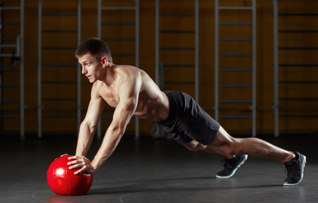 Muscular man doing sport exercises with red medicine ball. Stock Photo