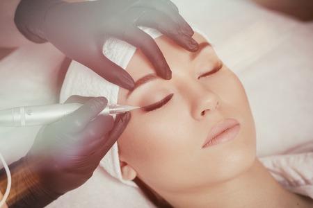 Cosmetologist making permanent makeup at beauty salon.