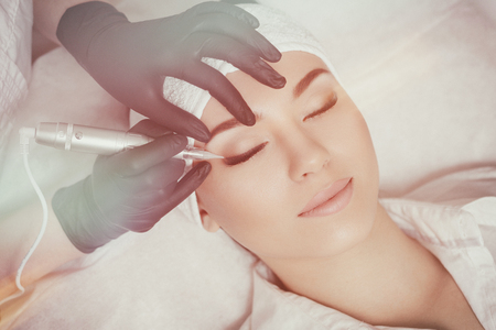 cosmetologist: Professional cosmetologist wearing black gloves making permanent makeup