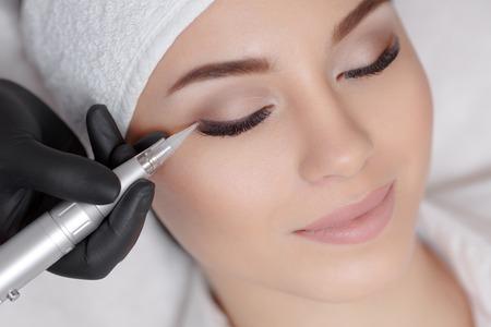 Cosmetóloga haciendo maquillaje permanente en el salón de belleza Foto de archivo