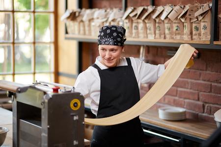 tortellini: Woman cooks dough on machine for making pasta