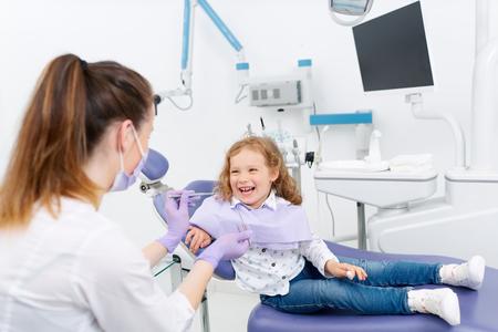 치과 의사에게 미소 짓는 작은 환자 스톡 콘텐츠