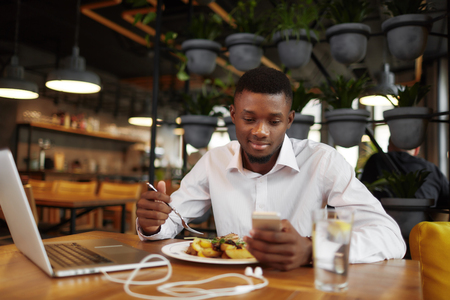 African businessman working and having dinne at restaurant.