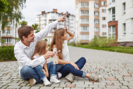 Happy family in front of new apartment building Stockfoto