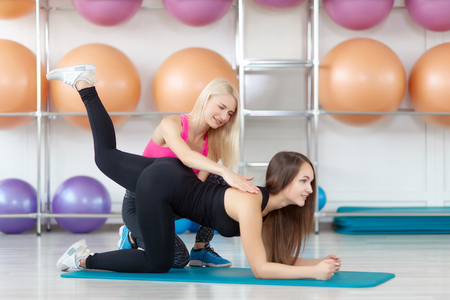 Young woman exercising with her fitness instructor Stock Photo