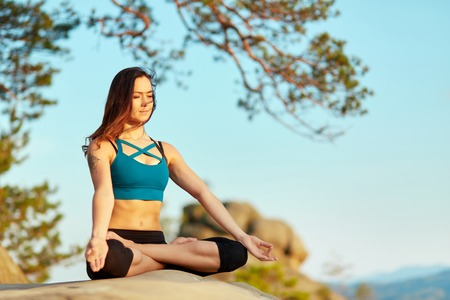 Young woman practiving yoga outdoors