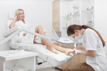 Podiatrist making procedure for client foot with special equipment. Stock Photo