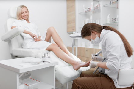 Podologe, der Verfahren für lächelnden Klientenfuß macht.