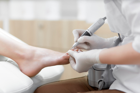 Doctor in gloves making procedure for foot with special equipment.