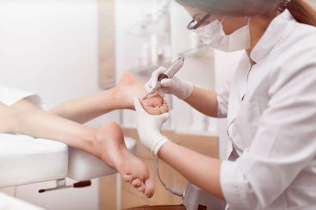 Podiatrist using special grinding equipment.