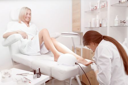 Specialist in white cleaning cuticle around nails on feet and po Stock Photo