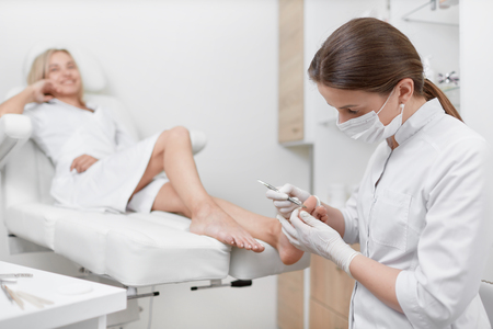 Podiatrist doctor cleaning foot from callus. Stock Photo