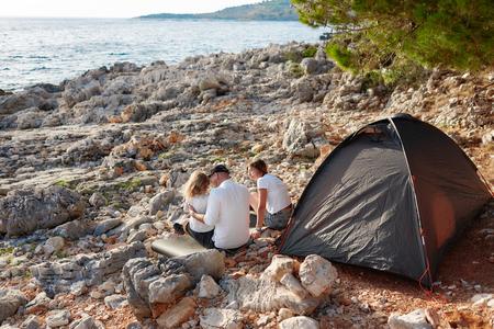 Back view of family, sitting near tent on stone seacoast. Standard-Bild - 106357487