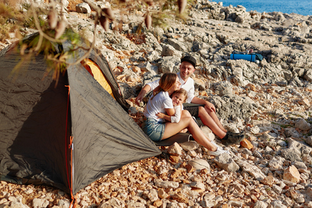 Side view of family, sitting on ground pad near tent on stone seacoast. Фото со стока