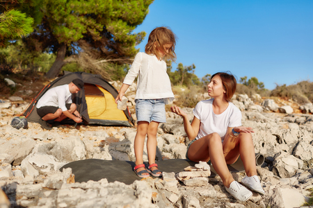 Mom and little girl imposes stone one by one at beach. Standard-Bild - 106357491